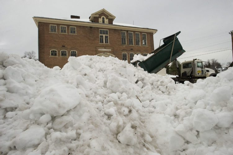 A dump truck releases a load of snow from the Shenandoah County Social Services lot on North Main Street in Woodstock last Monday.  Area officials are now calculating storm clean-up costs. Rich Cooley/Daily